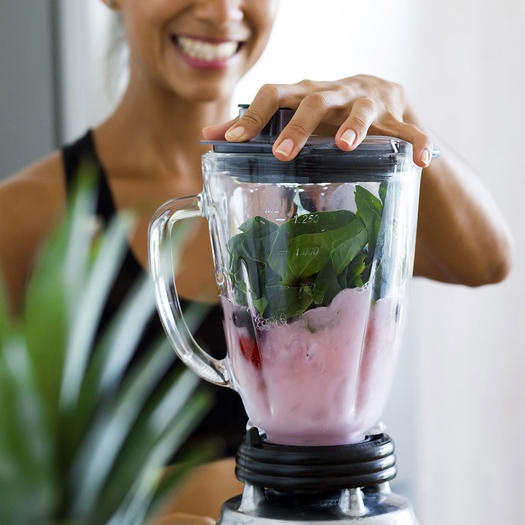 woman making a smoothie for breakfast