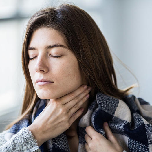 woman taking natural remedy for sore throat from cold or flu