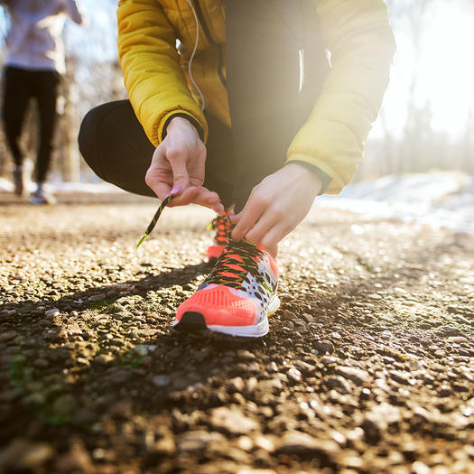 woman tying shoes to go on a run benefits