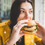 Woman eating burger after workout